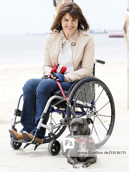 Woman sitting in wheelchair at waterfront with dog on leash
