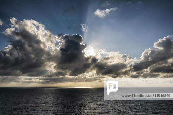Sunbeams behind clouds over ocean