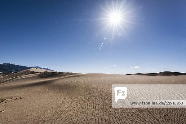 Sun in blue sky over sand dunes