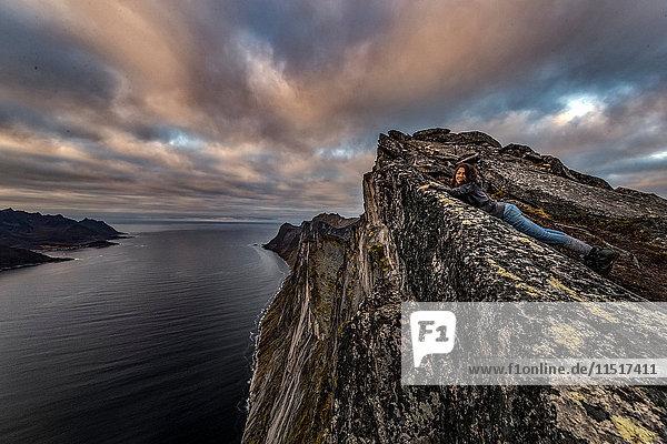 Frau schaut im Herbst vom Segla Peak auf der Insel Senja auf das Meer hinaus  Arktis Norwegen