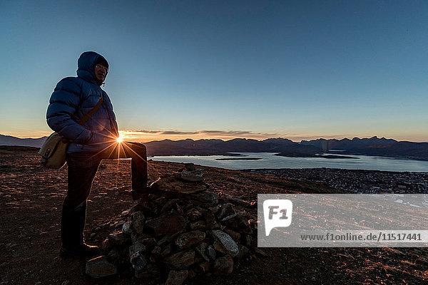 Mann besteigt im Herbst einen Gipfel bei Tromso  arktisches Norwegen