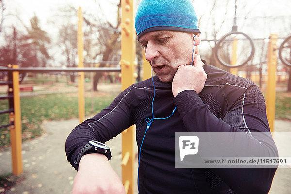 Reifer Mann  draußen  Pulsfrequenz prüfen  auf die Uhr schauen