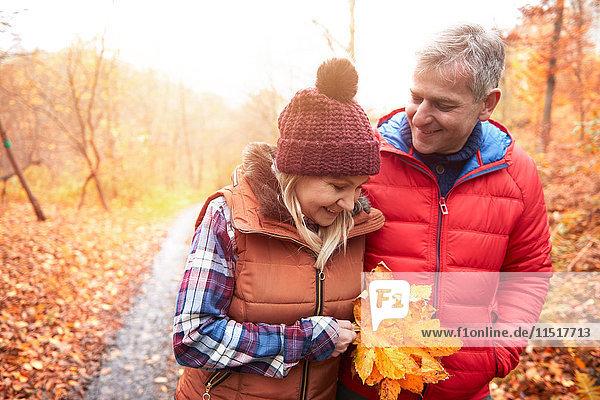 Ein reifes Paar geht im Herbst auf einem ländlichen Pfad