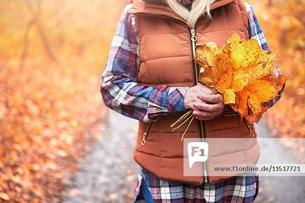 Frau im Freien stehend  Herbstblätter haltend  Mittelteil