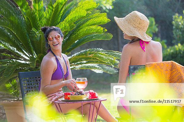 Frauen in Badebekleidung bei einem Drink