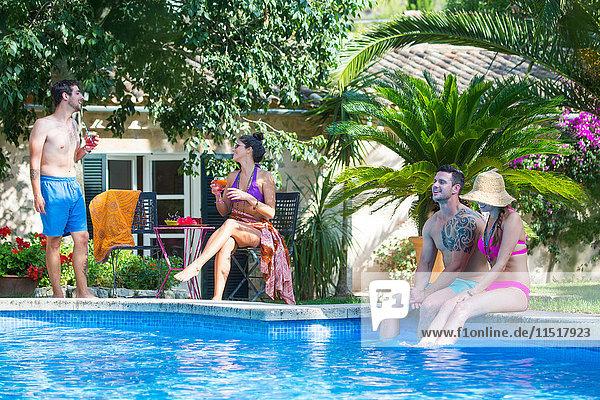 Am Pool sitzende Freunde