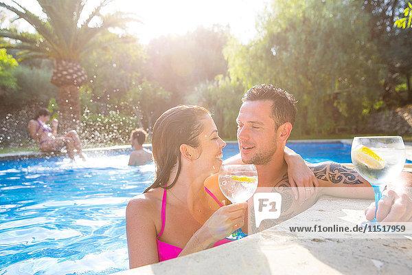 Ehepaar im Schwimmbad bei einem Drink