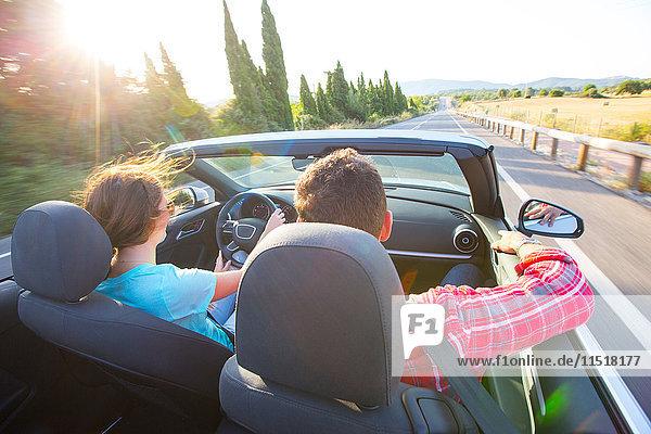 Rückansicht eines Cabrio-Paares auf einer sonnenbeschienenen Landstraße  Mallorca  Spanien