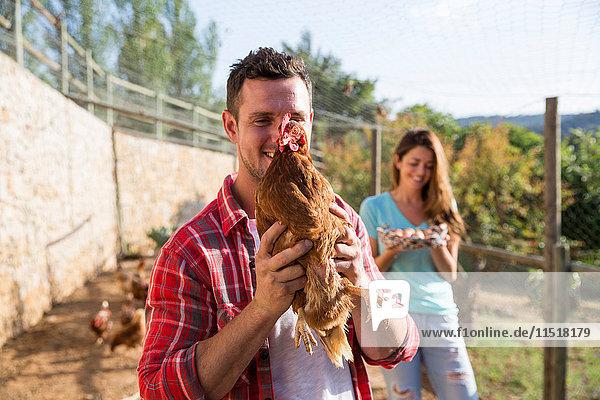 Porträt eines Biobauern mit freilaufenden Hühnern