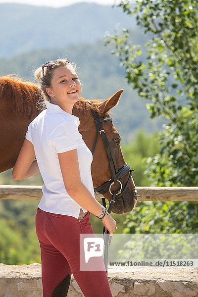 Porträt einer jungen Bräutigamsfrau mit Pferd in ländlichen Ställen