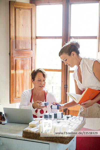Unternehmerin prüft die Qualität von Seifenstücken im Büro einer handgefertigten Seifenwerkstatt