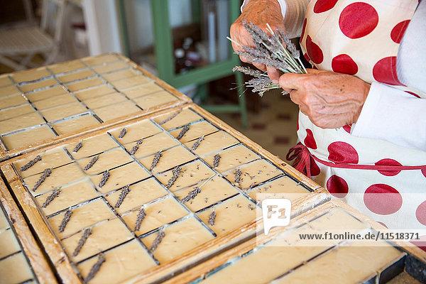 Mittelteil einer Frau  die in einem Workshop für handgemachte Seife getrockneten Lavendel auf Seifenstücke aufträgt Mittelteil einer Frau, die in einem Workshop für handgemachte Seife getrockneten Lavendel auf Seifenstücke aufträgt