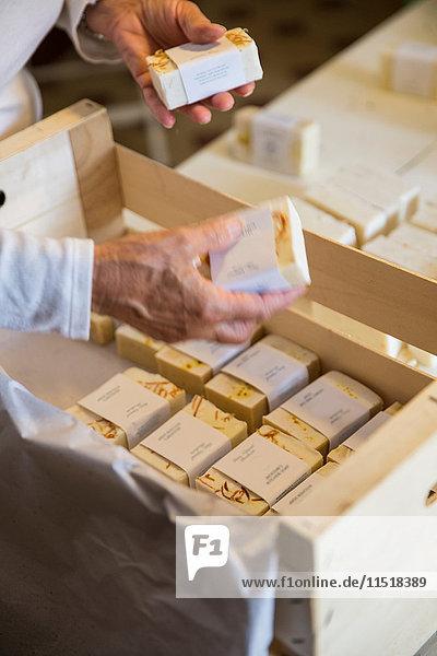 Frauenhände beim Verpacken von Seifenstücken in der Werkstatt für handgemachte Seife
