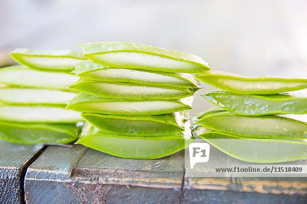 Gestapelte  in Scheiben geschnittene Aloe-Blätter auf dem Tisch in der Werkstatt für handgemachte Seife Gestapelte, in Scheiben geschnittene Aloe-Blätter auf dem Tisch in der Werkstatt für handgemachte Seife