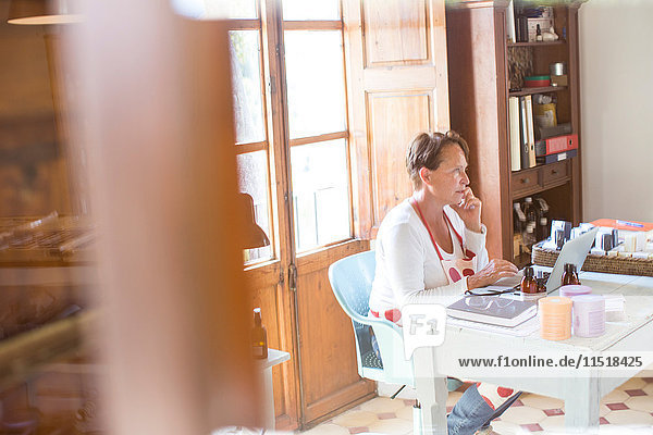 Woman talking on smartphone whilst using laptop in handmade soap workshop office