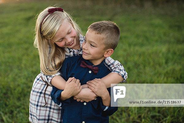 Sister hugging brother smiling
