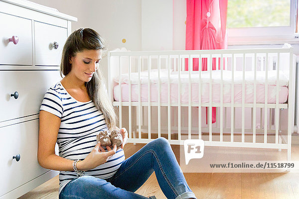 Pregnant woman sitting on floor in nursery holding baby shoes smiling