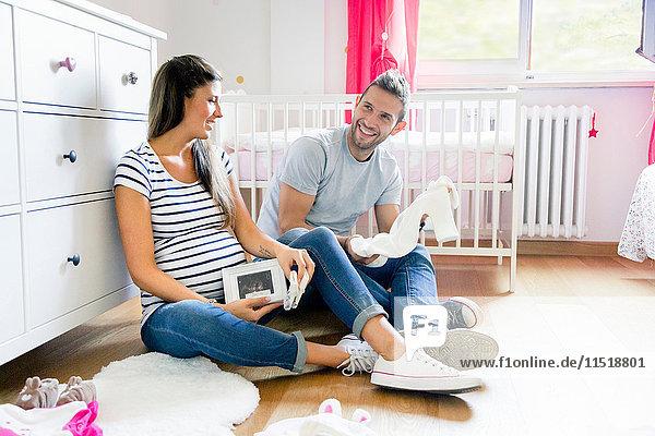 Schwangeres Paar sitzt auf dem Boden im Kinderzimmer und bereitet Babykleidung vor Schwangeres Paar sitzt auf dem Boden im Kinderzimmer und bereitet Babykleidung vor