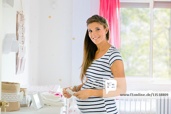 Porträt einer schwangeren Frau im Kindergarten  die lächelnd in die Kamera schaut