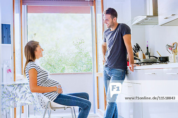 Pregnant couple in kitchen talking