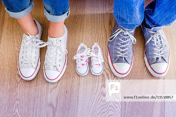Cropped view of baby shoes between man and woman's feet