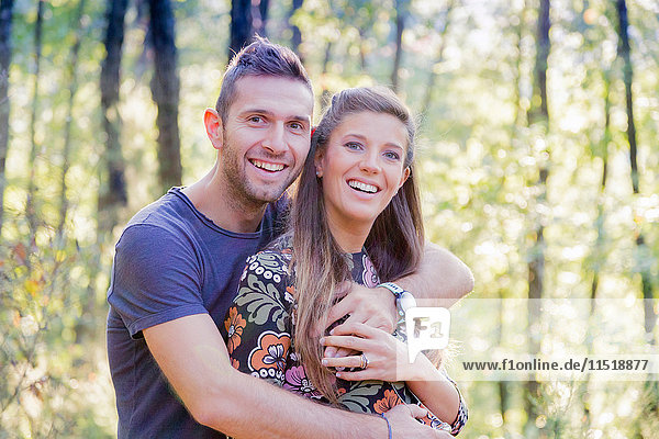 Couple in forest hugging looking at camera smiling