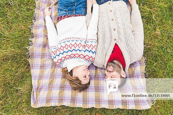Mittleres erwachsenes Paar im Park  auf Decke auf Gras liegend  Blick nach oben