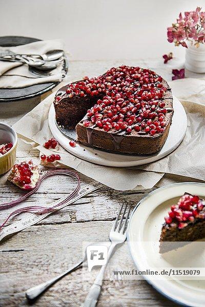 Herzförmiger Schokoladenkuchen mit Schokoladenglasur und Granatapfelkernen