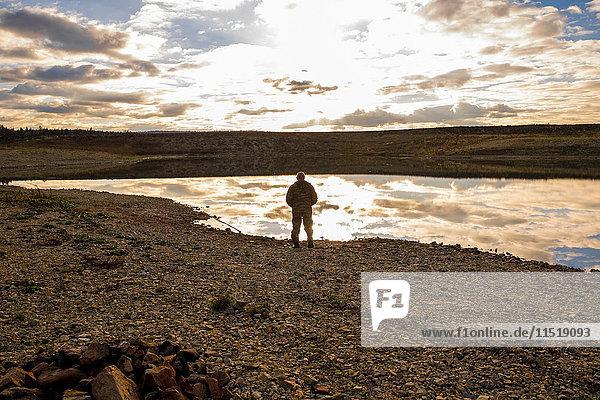 Mann betrachtet Landschaft vom Wasser aus  Ural  Russland