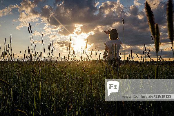 Frau bei Sonnenuntergang auf dem Feld