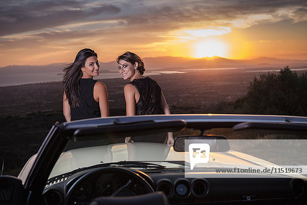Two young sitting on bonnet of convertible car  looking over shoulder  rear view