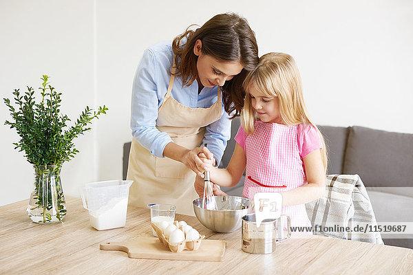 Mutter hilft der Tochter  die Zutaten in der Schüssel zu verquirlen.