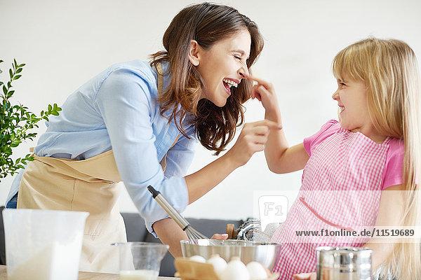 Mutter und Tochter backen zusammen  albern herum