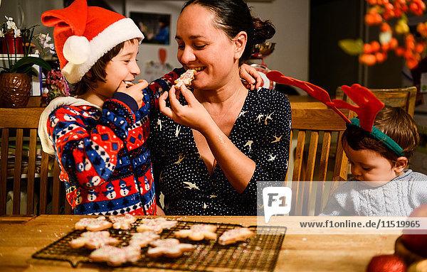 Mutter und zwei Söhne essen am Tisch selbstgebackene Weihnachtsplätzchen