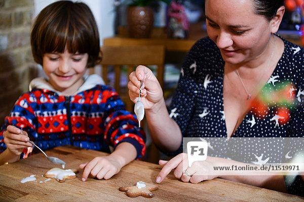 Mutter und Sohn glasieren am Tisch selbstgebackene Weihnachtsplätzchen