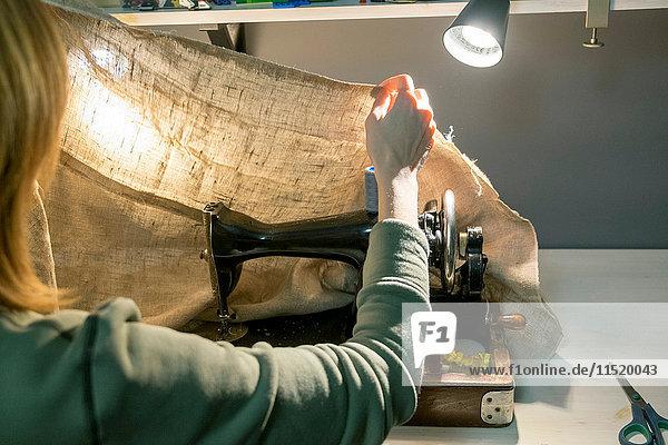 Rückansicht der Näherin  die das Sackleinen an der Nähmaschine vorbereitet