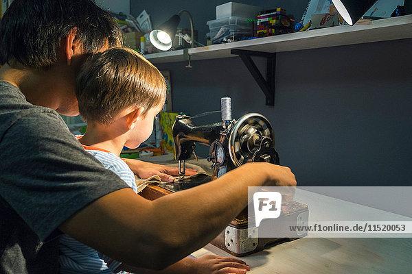 Über-Schulter-Ansicht eines Jungen mit einem Vater  der lernt  den Griff einer Nähmaschine zu drehen