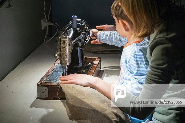 Über-Schulter-Ansicht eines Jungen mit einer Mutter  die lernt  den Griff einer Nähmaschine zu drehen