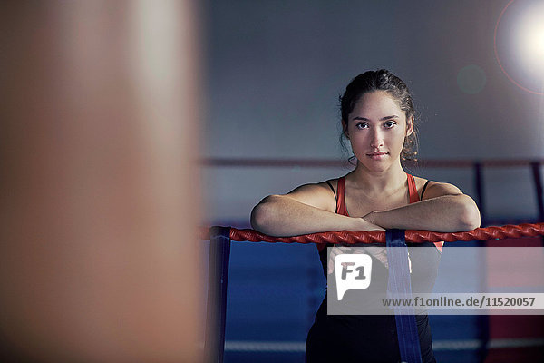 Portrait of young female boxer leaning on boxing ring ropes