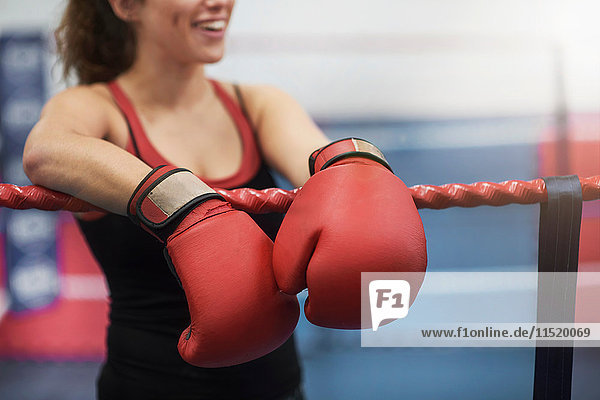 Cropped shot of young female boxer leaning on boxing ring ropes