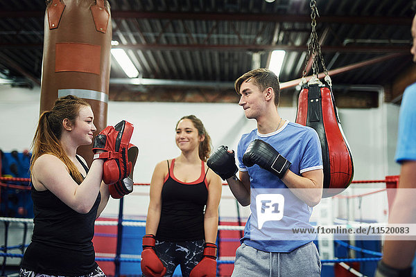 Male boxer training  poised to punch teammates punch mitt