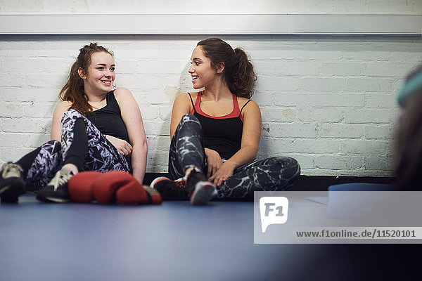 Zwei junge Boxerinnen sitzen auf dem Boden der Turnhalle und unterhalten sich