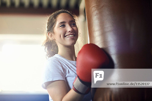 Young female boxer punching punch bag in gym