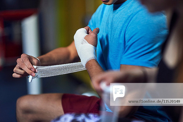 Cropped shot of young male and female boxers bandaging hands