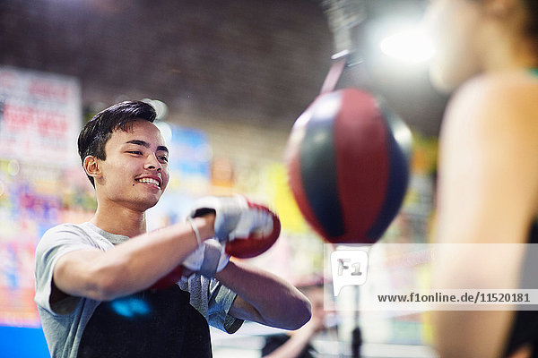 Young male boxer punching speed bag in gym