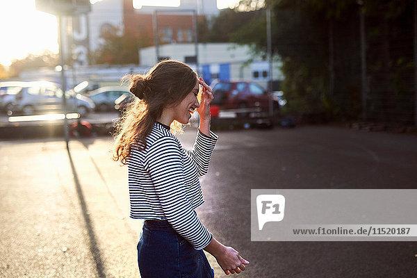 Junge Frau geht auf sonnenbeschienener Straße