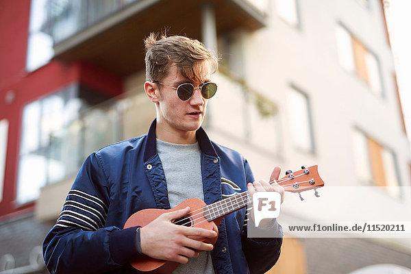 Young man on playing ukulele