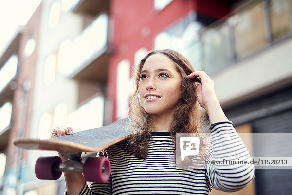 Young female skateboarder on street carrying skateboard on shoulder