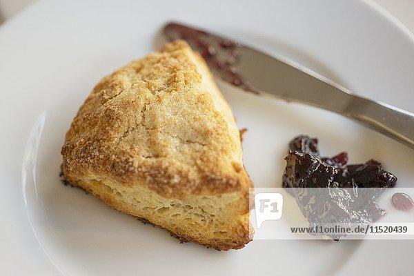 Buttermilch-Scone mit Schwarzkirschenkonfitüre auf Teller mit Messer