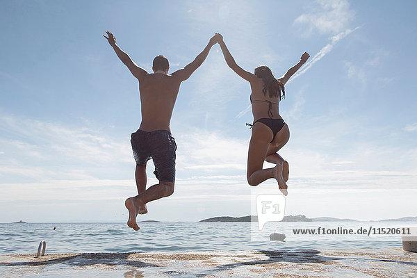 Junges Paar springt ins Meer  Rückansicht  Orebic  Kroatien